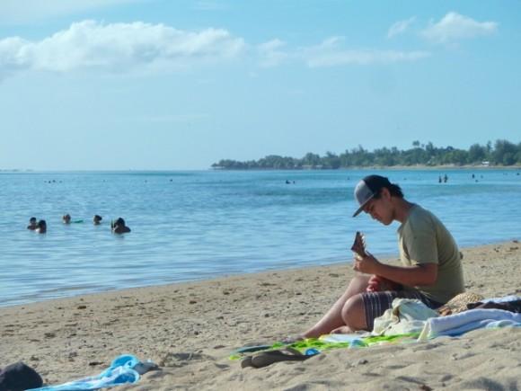 Joueur d'ukulele sur la plage publique.